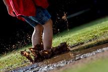 Child splashing in a mud puddle.