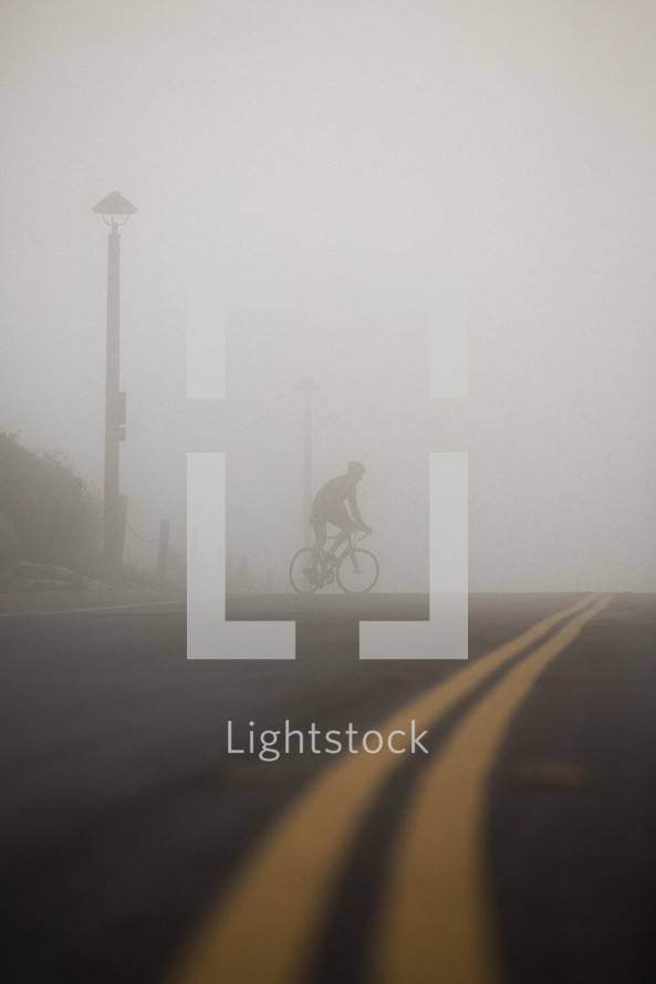 man riding a bicycle across the street under thick fog