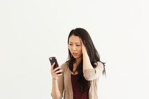 a stressed woman looking at a cellphone