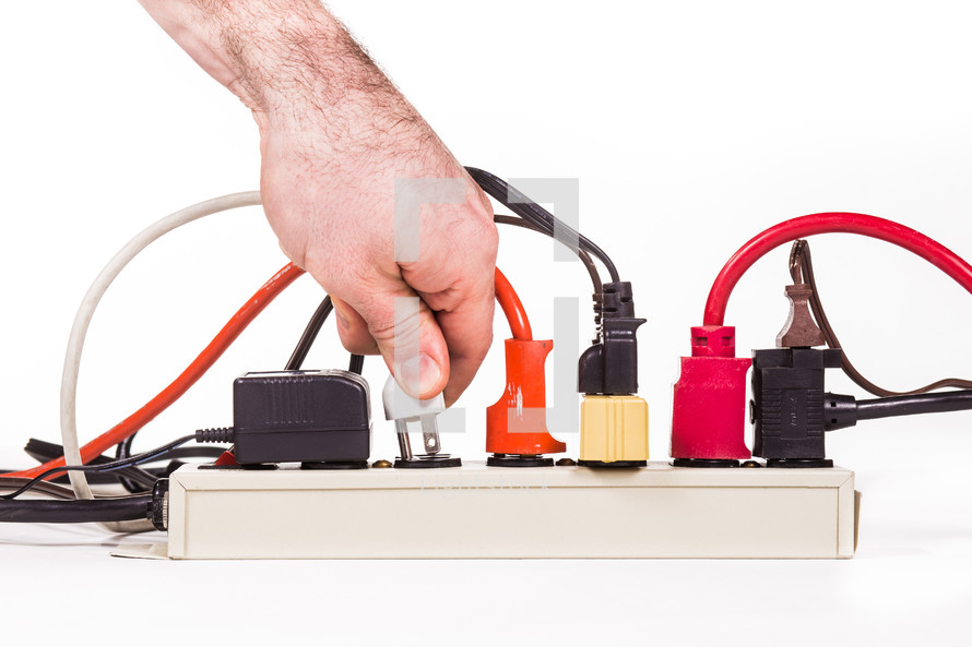 A hand plugging in plugs into a power strip