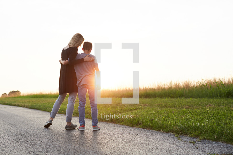 a mother with her arm around her son standing outdoors