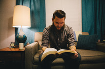 A man reading a Bible while sitting on a couch in his living room.