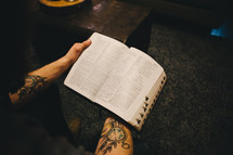 Man's arms holding an open Bible.