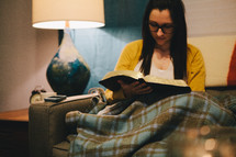 A woman sitting on a couch under a warm blanket reading a Bible.