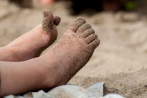 child's feet in the sand