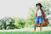 a woman walking through a field of grass