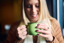 a woman in a sweater and scarf drinking coffee