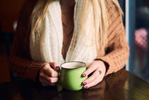 a woman in a sweater holding a coffee cup