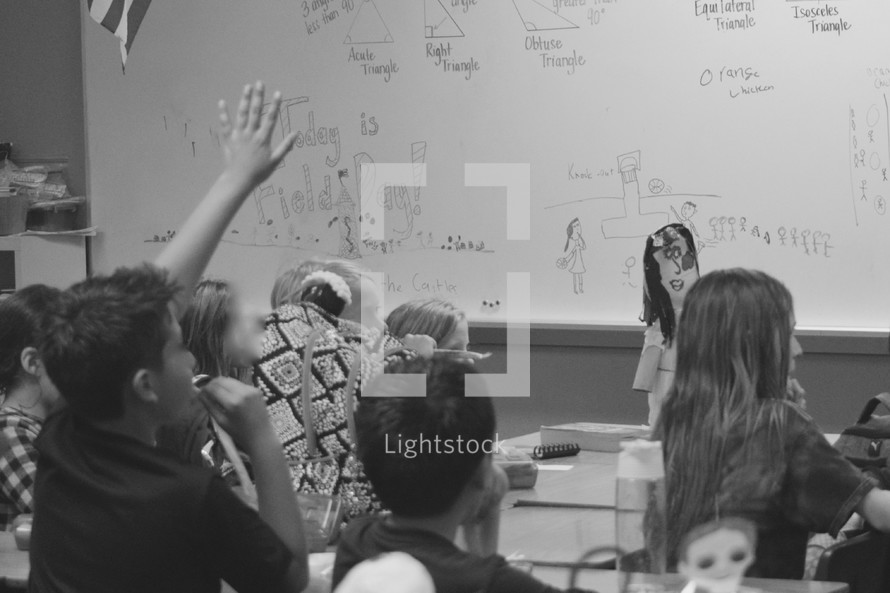 kids in a classroom with hands raised answering questions