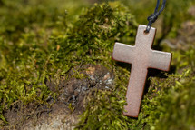 wooden cross necklace on moss