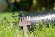 wooden cross necklace and Bible in the grass