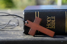 wooden cross necklace and Bible