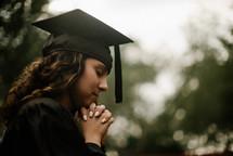 a praying female graduate
