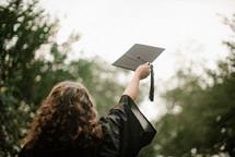 female graduate tossing her graduation cap