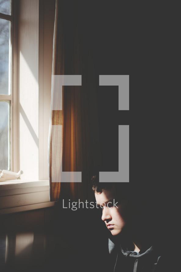 man's sad face in sunlight through a window