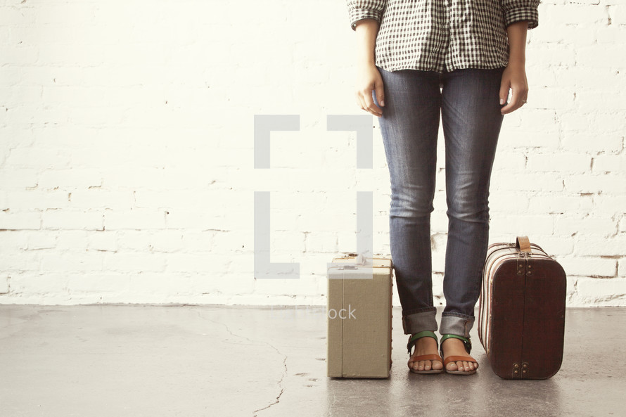 Girl standing ready to go with packed luggage.
