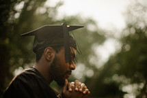 a male graduate praying