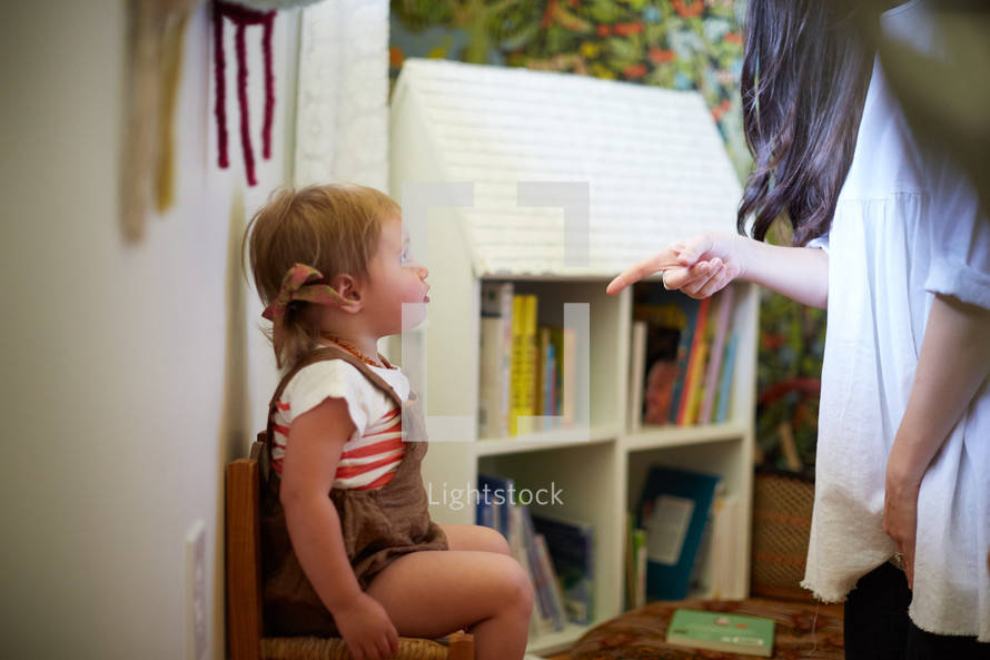 a toddler girl being disciplined by her mom.
