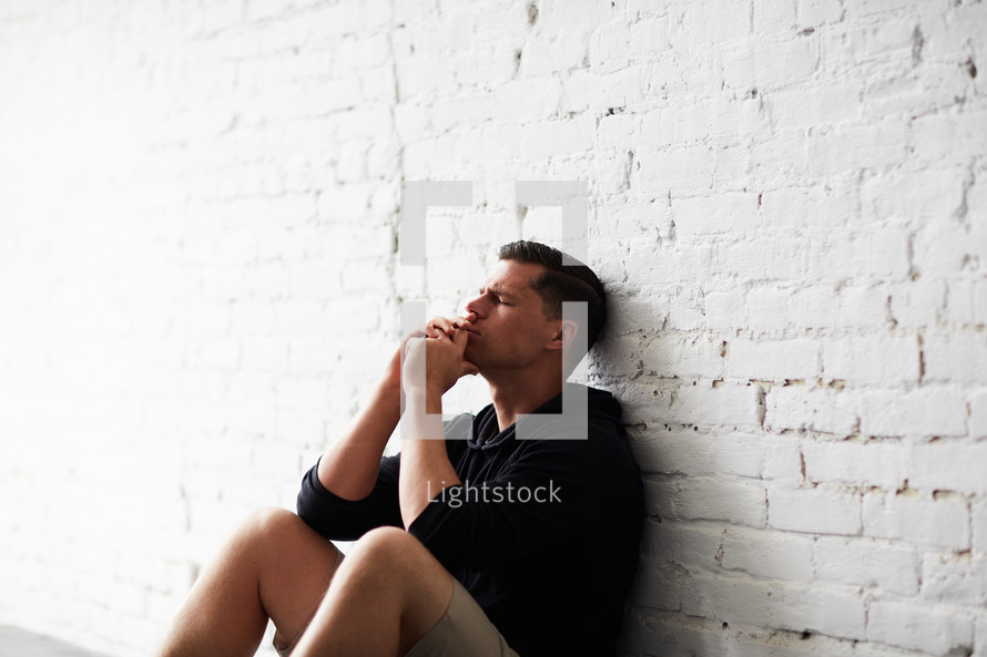 a man sitting alone leaning against a wall praying