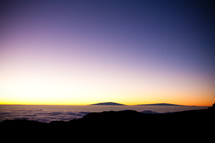 horizon over mountaintops in the clouds at dawn