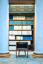 a chair in front of books on a bookshelf in a library