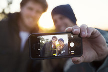 friends taking a selfie together at sunset.