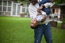 A father holding and playing with his young son in the back yard.