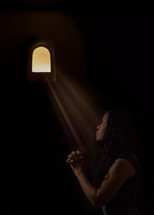sunlight through a small window shining on a woman's face as she prays