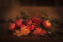 apples, red berries, and fall leaves on a wood table