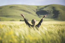 a woman standing in a field of wheat with raised hands
