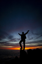 a man standing on a rock along a shore at sunset with hands raised