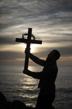 man holding up a cross with crown of thorns at sunset