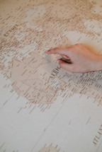 finger pointing to a world map