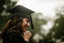 a female praying graduate