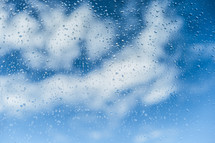 clouds in a blue sky and water drops on glass