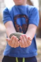 a boy holding a stone