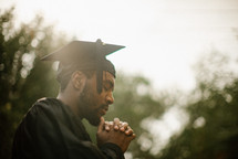 a praying male graduate