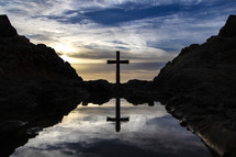 silhouette of a cross at sunset near a tide pool