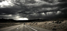 Highway road approaching storm. black and white desert mountains
