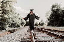 graduate balancing walking on train tracks
