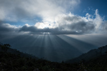 Rays of sunlight on a valley, through the clouds.