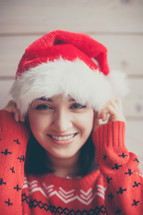 a woman in a Santa hat and Christmas sweater