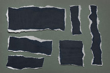 Black shapes beneath torn gray paper.