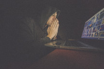 A man in a hooded sweatshirt praying in front of a computer screen.