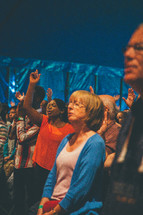 People  standing and worshipping at a church service.