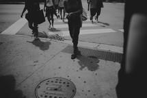 people crossing a street at a crosswalk
