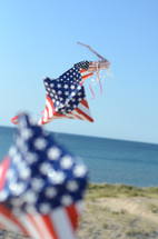 American flag themed kite flying on a beach