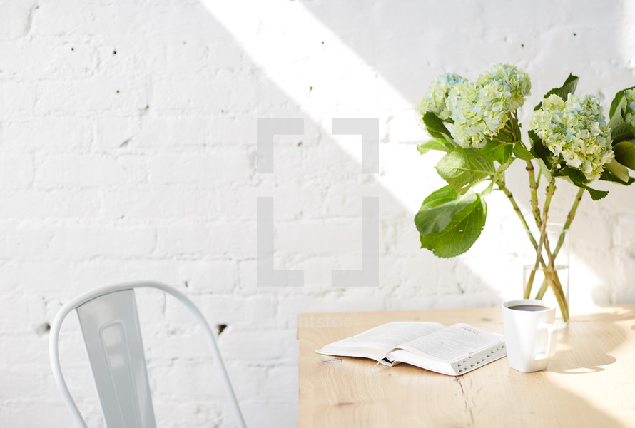 hydrangeas in a vase, open Bible, and coffee cup on a table