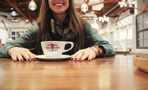 woman with hands on a table in front of a coffee cup