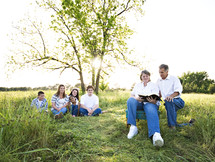 family reading the Bible together outdoors